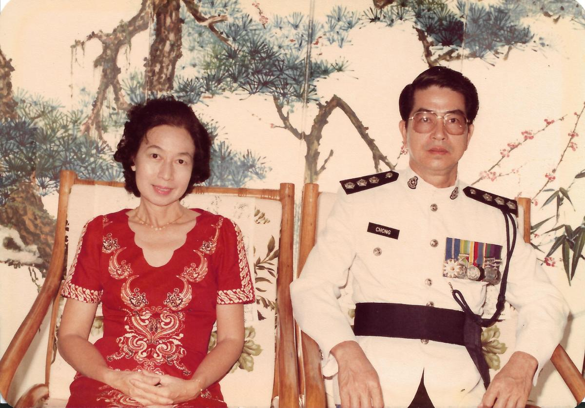 Khim and Her Husband in Uniform Sitting in Front of the Painted Folding Screen at Home (Jan 1984)
