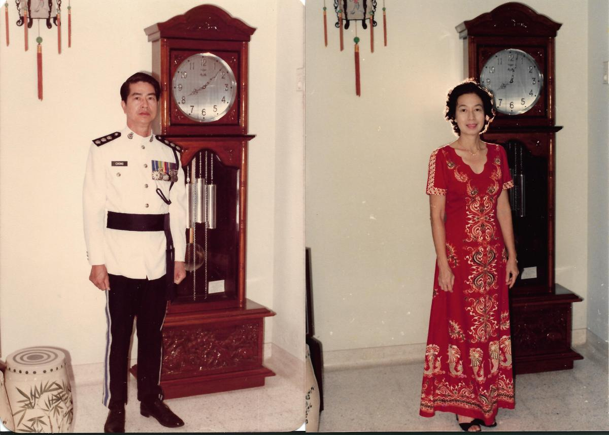 Khim and Her Husband Standing in Front of the Grandfather Clock at Home (Jan 1984)